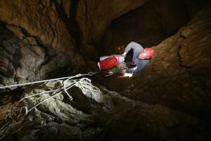 Robert podczas opuszczania pompy na prożku w początkowych partiach jaskini. © Paweł Ruda